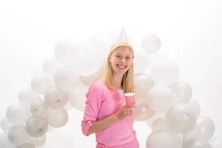 Balloon. Party mood. Beautiful girl in birthday hat with balloons. Girl in pajama celebrate pajama party. Smiling woman in party balloons. Happy birthday celebration. Party celebration with balloons Stok Fotoğraf - 134339890