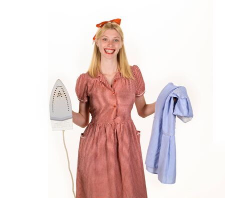 Girl holding iron in hand. Housekeeper woman in uniform with iron in hand. Beautiful woman holds steam iron. Housework and household concept - housewife ironing clothes. Retro woman ironing clothing