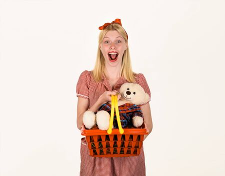 Happy woman with shopping basket. Shopping. Woman in shopping concept. Woman in supermarket. Girl holds basket in supermarket. Smiling girl holds basket with teddy bear. Sale, shopping, consumerism Stok Fotoğraf - 134339897