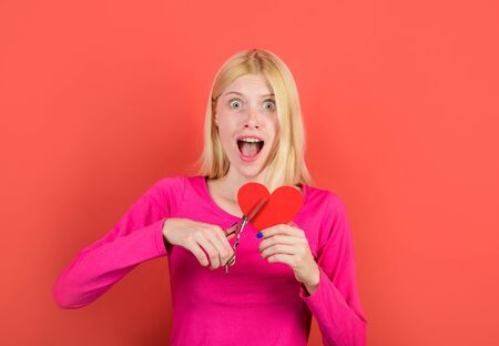Woman cuts heart by scissors. Beautiful girl cuts with scissors red heart. Concept of breaking relations, quarrels and divorce. Pair diverges. Loss of feelings for your loved one. Bad relationships