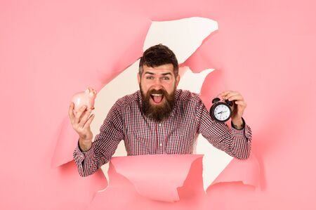 Saving money. Business success concept. Businessman holds piggy bank and alarm clock. Time is money concept. Happy bearded man looking through hole in pink paper holds piggy-bank and clock. Finance Stok Fotoğraf - 134781028