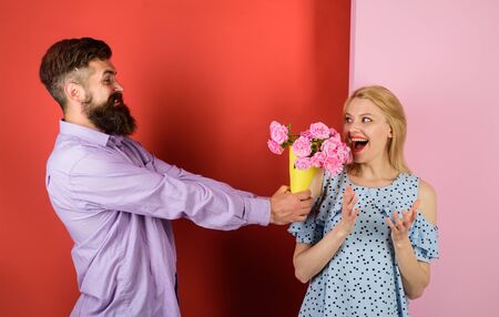 Couple in love with bouquet of flowers. Handsome bearded man gives bouquet of flowers to woman. Love, relationship, dating. Man giving bouquet of roses to his girlfriend. Beautiful romantic couple