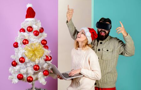 New Year, Christmas, future and technology concept. Woman in santa hat with laptop. Bearded man in virtual 3D glasses at christmas. Virtual reality mask. 3d technology, virtual reality, entertainment 写真素材