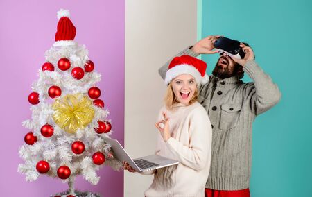 3d technology, virtual reality, entertainment. Woman in santa hat with laptop. Bearded man in virtual 3D glasses at christmas. Virtual reality mask. New Year, Christmas, future and technology concept 写真素材