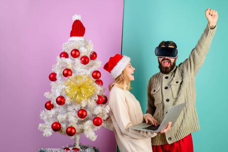 Bearded man in virtual 3D glasses. Woman in santa hat with laptop. Virtual reality mask. New Year, Christmas, future and technology concept. 3d technology, virtual reality, entertainment. Stok Fotoğraf - 134781039