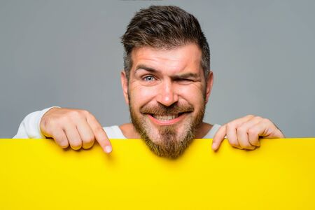 Smiling bearded man holds blank billboard. Happy man holds empty placard. Businessman with blank poster. Advertising. Man showing blank board with copy space. Attractive guy holds advertising banner Stok Fotoğraf - 134781041