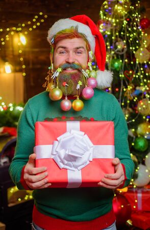 Funny wintertime. Bearded man in santa hat with decorated beard for New Year holiday. Santa Claus man hold Christmas gift. Merry Christmas. New year. Christmas beard decorations. Christmas decoration 写真素材
