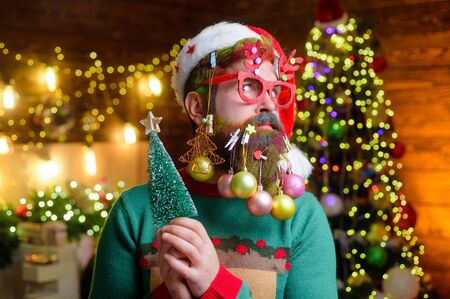 Christmas or new year celebration. Winter holidays. New year guy in Santa hat with decoration balls in beard. Christmas beard style. Bearded new year man in party glasses holds small Christmas tree