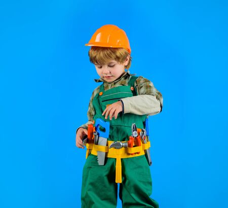 Tools for building. Little boy in builders uniform with tools. Little boy in helmet and tools. Kid as construction worker. Little boy plays construction worker. Builder. Little repairman. Child game 写真素材