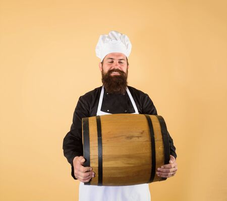 Bearded brewer in apron with barrel. Viticulture concept. Attractive bearded man with wooden barrel of wine or beer. Chef man holds wooden wine barrel. Handsome man winemaker holds wooden wine barrel 写真素材