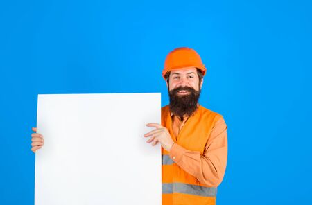 Construction worker, engineer, architect with blank board. Builder, repairman in protective helmet holds empty board with space for text. Man builder holds advertising banner, billboard, sign board