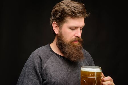 Craft beer at restaurant. Beer time. Bearded man tasting fresh delicious beer. Oktoberfest. Holliday, drinks, alcohol, leisure concept. Bearded man hold glass with craft ale. Beer in Germany. Alcohol