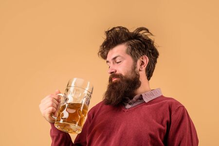 Craft beer at restaurant. Bearded man tasting fresh delicious beer. Oktoberfest. Holliday, drinks, alcohol, leisure concept. Bearded man hold glass with craft ale. Beer in Germany. Alcohol. Beer time