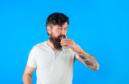 Healthy lifestyle. Health care concept. Drinking water. Handsome bearded man drinking glass of fresh water. Sportsman drinking water in morning. Hydration and drink concept. Bearded man drinks water Stok Fotoğraf - 134781069