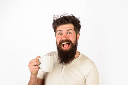 Happy man holds coffee. Man holds cup with hot tea. Morning refreshment. Awaking. Bearded man with cup of coffee. Morning routine. Wake up. Sleepy man having cup of coffee in kitchen. Morning coffee
