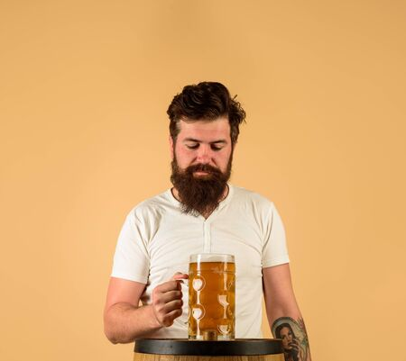 Bearded brewer with wooden barrel of beer and mug of beer. Oktoberfest. Holliday, drinks, alcohol, leisure concept. Bearded man hold glass and barrel with craft beer. Brewer. Craft beer at restaurant