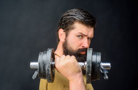 Fitness. Strong man training with dumbbells. Bearded man exercise with dumbbell. Handsome athlete man with dumbbells. Muscular sportsman with dumbbells training at gym. Sportsman making weightlifting