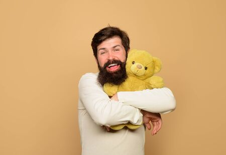 Man holds Teddy bear plush toy. Smiling man hugs teddy bear. Holiday celebration. Birthday or anniversary. Bearded man with plush toy. Teddy bear. Man with fluffy teddy bear. Gift and present concept