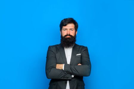 Serious businessman standing with crossed arms. Stylish handsome business man stands with folded arms. Attractive bearded man portrait. Handsome man in suit. Male fashion concept. Stylish bearded man