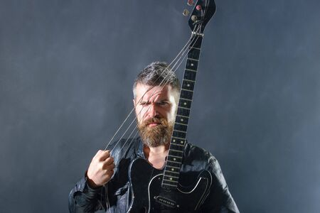 Music hobby. Guitar player in jacket with electric guitar. Rock or punk music concert. Bearded man with guitar. Concert tour. Handsome man with guitar. Fashionable guitarist with instrument