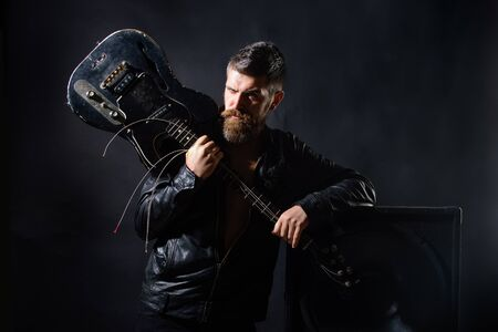 Concert tour. Attractive man with guitar. Fashionable guitarist with classic instrument. Music hobby. Guitar player in jacket with electric guitar. Rock or punk music concert. Bearded man with guitar