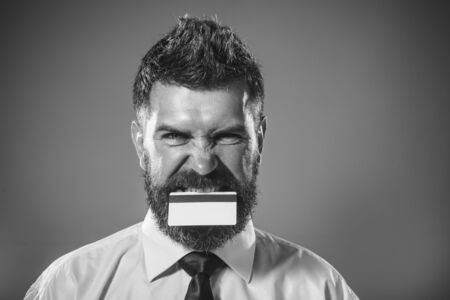 Banking service. Businessman with creditcard in mouth. Finance, payment, transaction, money. Online shopping. E-money. Cashless payment. Internet bank. Business idea concept. Bank-card with magstripe 写真素材