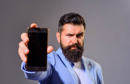 Businessman holds smartphone. Businessman show smart phone with blank screen. Business man shows mobile phone. Business, communication, internet, technology concept. Bearded man in suit showing phone