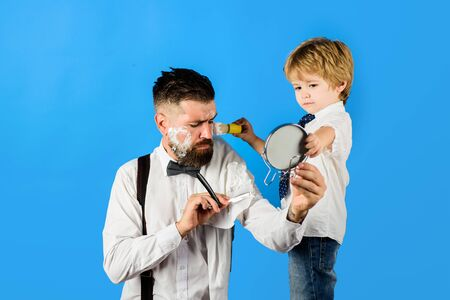 Little barber. Barbershop concept. Salon for men. Look perfect in barber shop. Assistant for dad. Fathers day. Little boy holds mirror for father. Barber shaving bearded man in barbershop. Beard care Stok Fotoğraf - 134781098