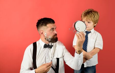 Fathers day. Little boy holds mirror for father. Barber shaving bearded man in barbershop. Beard care. Little barber. Barbershop concept. Salon for men. Look perfect in barber shop. Assistant for dad 写真素材
