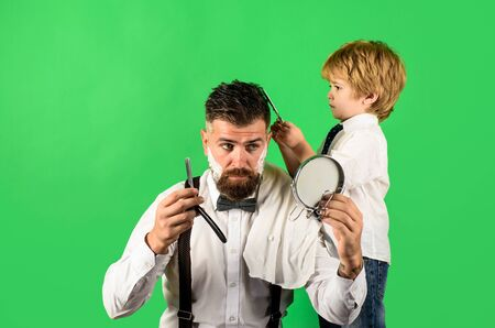 Assistant barber. Hairdresser for father. Trendy and stylish father and son. Professional hairstylist. Hairdresser work. Beard man visiting hairstylist in barber shop. Cute son haircuts his father