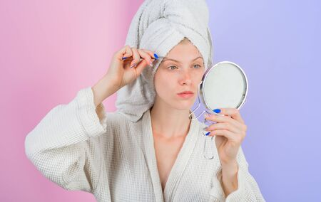 Woman pluck eyebrows looking in mirror. Epilate eyebrows. Makeup process. Eyebrows beauty care concept. Beauty tools. Woman pulls out eyebrows with tweezers. Correction procedure in beauty salon