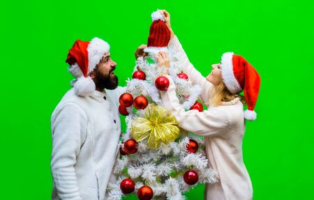 Family getting ready to celebrate New Year. Happy couple preparing for winter holidays. Happy girlfriend decorating Christmas tree with boyfriend. Happy family in Santa hats decorating Christmas tree Stok Fotoğraf - 134781110