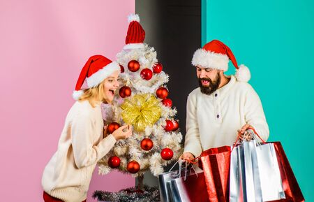 Christmas sales. Happy couple shopping for christmas in wintertime. Happy couple with shopping bags near christmas tree. Christmas and New Year shopping. Shopping, sale, gifts, christmastime concept