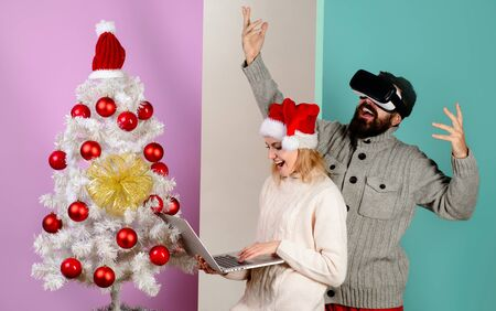 Woman in santa hat with laptop. Bearded man in virtual 3D glasses at christmas. Virtual reality mask. New Year, Christmas, future and technology concept. 3d technology, virtual reality, entertainment 写真素材