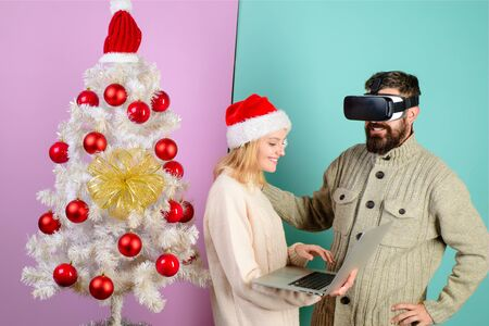Virtual reality mask. New Year, Christmas, future and technology concept. Woman in santa hat with laptop. Bearded man in virtual 3D glasses at christmas. 3d technology, virtual reality, entertainment Stok Fotoğraf - 134781144