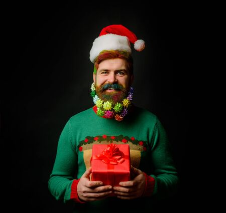 Santa man with Christmas gift box. Santa Claus holds present. New Year eve. Merry Christmas and happy New year. Wish you merry Christmas. Present box. Bearded man in Santa hat holds present gift box Stok Fotoğraf - 134781158
