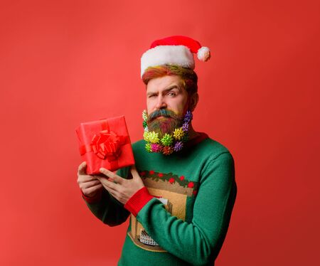 Merry Christmas and happy New year. Santa man with Christmas gift box. Santa Claus holds present. New Year eve. Present box. Wish you merry Christmas. Smiling man in Santa hat hold present gift box