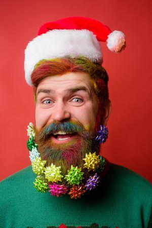 Smiling bearded man in Santa hat. New year fashion clothes. Christmas beard decorations. Santa Claus wishes Merry Christmas. Christmas celebration holiday. Christmas holidays. Happy new year. Stok Fotoğraf - 134781166