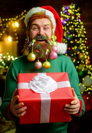 Christmas beard decorations. Funny wintertime. Christmas decoration. Bearded man in santa hat with decorated beard for New Year holiday. Santa Claus man hold Christmas gift. Merry Christmas. New year