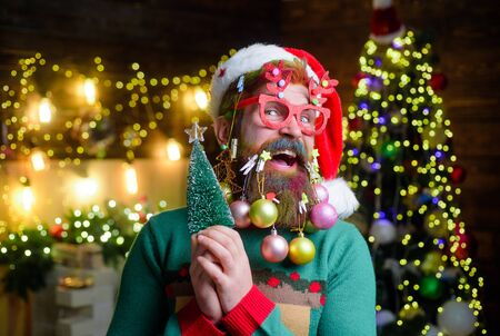 Winter holidays. New year guy in Santa hat with decoration balls in beard. Christmas or new year celebration. Christmas beard style. Bearded new year man in party glasses holds small Christmas tree