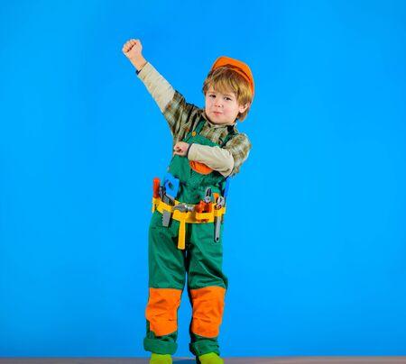 Little boy in helmet and tools. Little repairman. Kid as construction worker. Little boy in builders uniform with tools. Little boy plays construction worker. Builder. Child game. Tools for building 写真素材