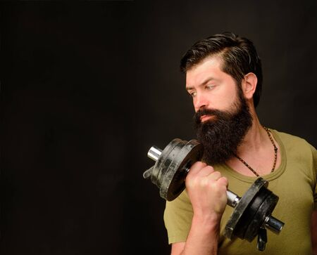 Bearded man exercise with dumbbell. Muscular sportsman with dumbbells training at gym. Handsome athlete man with dumbbells. Sportsman making weightlifting. Strong man training with dumbbells. Fitness Stock Photo