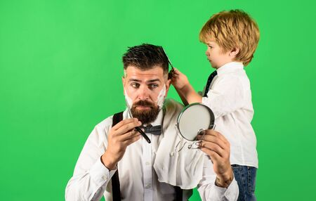 Hairdresser for father. Cute son haircuts his father. Trendy and stylish father and son. Professional hairstylist. Hairdresser work. Beard man visiting hairstylist in barber shop. Assistant barber Stock Photo