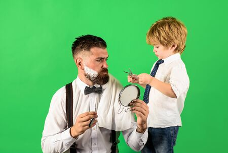 Professional hairstylist. Hairdresser work. Hairdresser for father. Cute son haircuts his father. Trendy and stylish father and son. Beard man visiting hairstylist in barber shop. Assistant barber