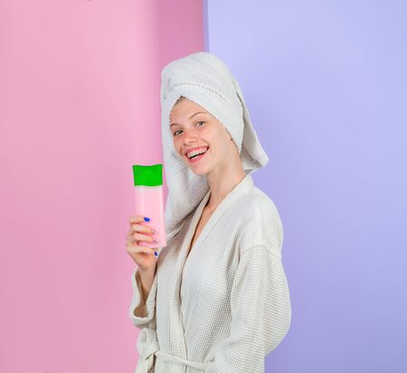 Hair care product. Cosmetics for hair. Beautiful woman with shampoo or conditioner. Woman with organic cosmetic for hair. Woman hold shampoo bottle. Woman in tender bathrobe. Haircare. Shampoo bottle