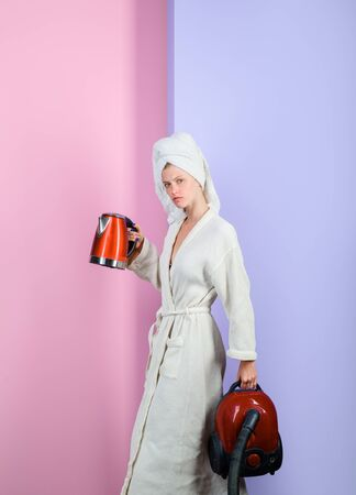Serious sexy woman with vacuum cleaner and kettle. Busy woman with vacuum cleaner and kettle at home. Housewife with vacuum cleaner and electric kettle in hands. Woman in bathrobe and towel on head Stock Photo