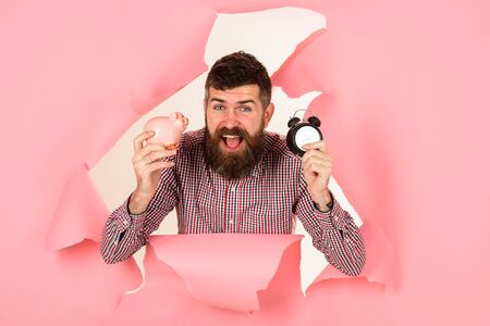 Time is money concept. Happy bearded man looking through hole in pink paper holds piggy-bank and clock. Saving money. Business success concept. Businessman holds piggy bank and alarm clock. Finance