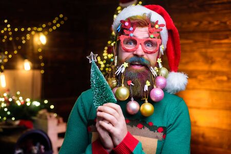 Bearded Santa Claus in party glasses holds small Christmas tree. Christmas beard style. Happy Santa with decoration balls in beard holds fir-tree. Merry Christmas and happy new year Stock fotó