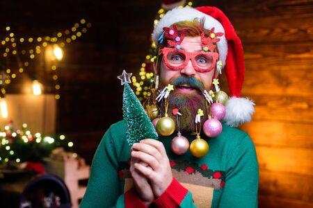 Der bärtige Weihnachtsmann in Partygläsern hält einen kleinen Weihnachtsbaum. Weihnachtsbart-Stil. Happy Santa mit Dekorationskugeln im Bart hält Tannenbaum. Frohe Weihnachten und ein glückliches Neues Jahr Standard-Bild