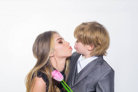 Birthday gift. Cute son congratulates mother on birthday. Brother give sister tulip flower. Celebration womens day. Son gives mom flower for holiday. Mothers day. Little son and mother happy together